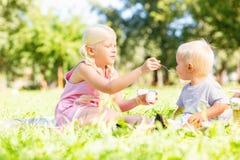 Une soeur plus âgée alimentant son petit frère mignon photographie stock