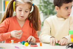 Une soeur plus âgée avec le jeune frère fait avec de l'argile figure, playin Image libre de droits