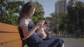 Une soeur plus âgée avec le jeune frère s'asseyant sur le banc en parc d'été Le garçon essayant sans succès d'emporter banque de vidéos