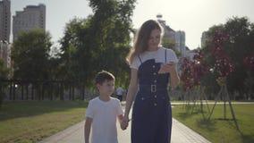 Une soeur plus âgée marchant avec le jeune frère tenant des mains en parc d'été Le garçon essayant d'emporter le téléphone portab banque de vidéos