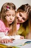 Une soeur plus âgée ou une mère enseigne à lire le plus jeune Image stock