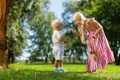 Une soeur plus âgée proposant des fruits à son frère image stock