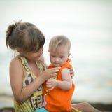 Une soeur plus âgée tient une belle fille avec la trisomie 21 Images stock