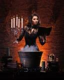 Une sorcière sexy de brune effectuant le poison Photos stock