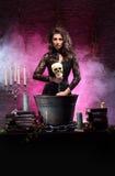 Une sorcière sexy de brune effectuant le poison photographie stock libre de droits