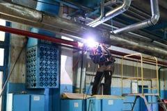 Une soudeuse d'ouvrier soude un trou dans le tuyau, la canalisation dans l'usine photographie stock