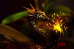 Une statue antique colorée de dragon tenant une boule de scintillement de lig Photo libre de droits