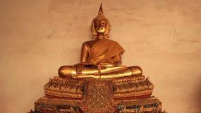 Une statue d'or de Buddhas sur le banc doré de stuc Photographie stock libre de droits