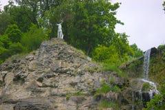 Une statue de cerfs communs près de cascade photographie stock libre de droits