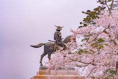 Une statue de Masamune Date présentant à cheval Sendai Castle dans des fleurs de cerisier de pleine floraison, parc d'Aobayama, S photographie stock