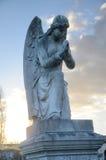 Une statue en pierre d'un ange à ailes au coucher du soleil Photos stock