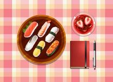 Une table avec des sushi, une boisson de cocktail, un ballpen et un carnet Photos stock