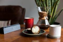 Une table basse moderne de salon avec une tasse de caf?, le livre, le comprim?, et un petit pain l?-dessus photos libres de droits