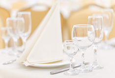 Une table d'ensemble dans le restaurant avec les verres vides et les couverts décorés des serviettes Photo libre de droits