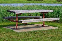 Une table de pique-nique en bois par une rivière Photographie stock