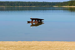 Une table de pique-nique placée dans l'eau à une plage Photographie stock