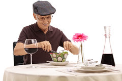 Aîné à une table de restaurant mangeant d'une salade Photo libre de droits