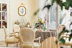 Une table de salle à manger et des fauteuils confortables dans une maison moderne avec une salle à manger légère image stock