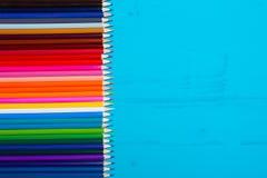 Une table en bois dans le bleu et des crayons colorés Vue de ci-avant image libre de droits