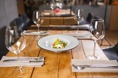 Une table en bois dans le restaurant, servi avec des verres au milieu, est un plat avec du fromage et le vegetab végétariens de m photographie stock