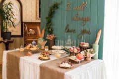 Une table rustique, scellée avec du fromage, des écrous, des fruits et des bonbons Un fond en bois Photo stock