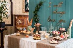Une table rustique, scellée avec du fromage, des écrous, des fruits et des bonbons Un fond en bois Photographie stock