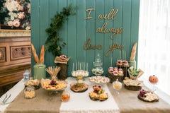 Une table rustique, scellée avec du fromage, des écrous, des fruits et des bonbons Un fond en bois Image libre de droits