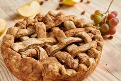 Une tarte aux pommes faite maison décorée des pommes coupées en tranches fraîches, des raisins et des raisins secs bruns sur le f Photo libre de droits