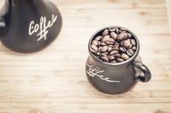 Une tasse avec des grains de café sur un fond modifié la tonalité en bois Photos libres de droits