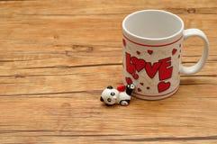 Une tasse blanche avec l'amour de mot là-dessus Photo libre de droits