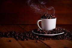 Une tasse blanche complètement de grains de café chauds photos stock