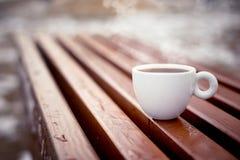Une tasse blanche de supports de café sur les conseils en bois dans l'environnement naturel pendant l'hiver photographie stock libre de droits