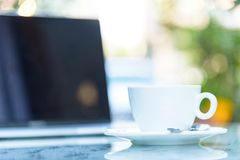 Une tasse blanche du café et de l'ordinateur portable prêts au travail pendant le matin Image stock
