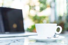 Une tasse blanche du café et de l'ordinateur portable prêts au travail pendant le matin Photographie stock