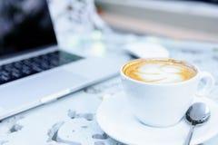 Une tasse blanche du café et de l'ordinateur portable prêts au travail pendant le matin Photo stock