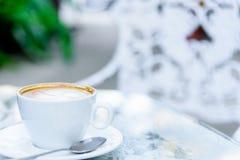 Une tasse blanche du café et de l'ordinateur portable prêts au travail pendant le matin Photo libre de droits