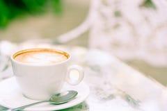 Une tasse blanche du café et de l'ordinateur portable prêts au travail pendant le matin Image libre de droits