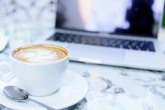 Une tasse blanche du café et de l'ordinateur portable prêts au travail pendant le matin Photos libres de droits