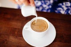Une tasse d'americano et de lait séparément photographie stock