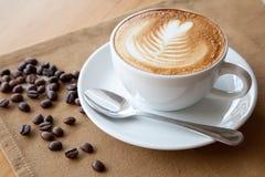 Une tasse d'art de latte et de grains de café photos stock