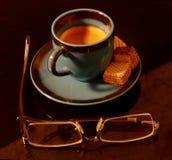 Une tasse d'expresso avec quelques festins et verres photo stock