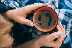 Une tasse d'orange de café dans des mains de la fille Photos stock