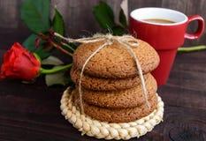 Une tasse de biscuits de cappuccino, roses et de farine d'avoine, attachés avec la ficelle sur le fond en bois foncé Photos stock