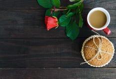 Une tasse de biscuits de cappuccino, roses et de farine d'avoine, attachés avec la ficelle sur le fond en bois foncé Photo stock