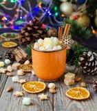 Une tasse de cacao chaud de Noël avec des lumières du ` s de nouvelle année de guimauve et des décorations, foyer sélectif Photos stock