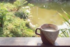 Une tasse de cacao chaud par le balcon en bois sur le fond de nature images libres de droits