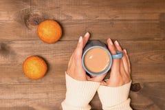 Une tasse de cacao dans les mains sur un fond en bois Chandail bleu et mini petits pains Photographie stock libre de droits