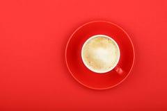Une tasse de café écumeuse de cappuccino de latte sur le rouge images libres de droits