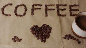 """Une tasse de café aromatique est placée sur le papier de métier avec le mot """"café """"présenté des grains de café banque de vidéos"""