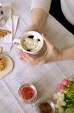 Une tasse de café avec des guimauves dans des mains femelles, bâtons de cannelle Photo libre de droits